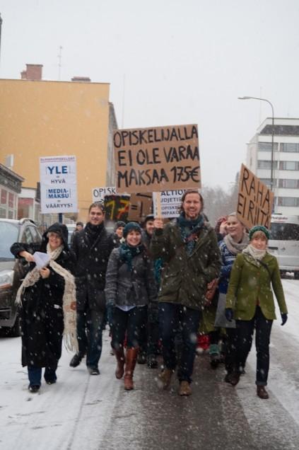 Jyväskylän yliopiston opiskelijat marssivat kyltit korkealla yläkaupungilta keskustan kompassille. Kulkuetta oli seuraamassa myös YLE:n autolla päärakennukselle kaartanut toimittaja (oikealla).