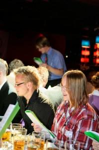 Varhaiskasvatuksen opiskelija Annemari Lindholm ja psykologian opiskelija Anssi Tikkanen pääsivät venyttelemään äänijänteitään taloustieteilijä Juha Lintulan (takana) aloitellessa sitsilaulua.